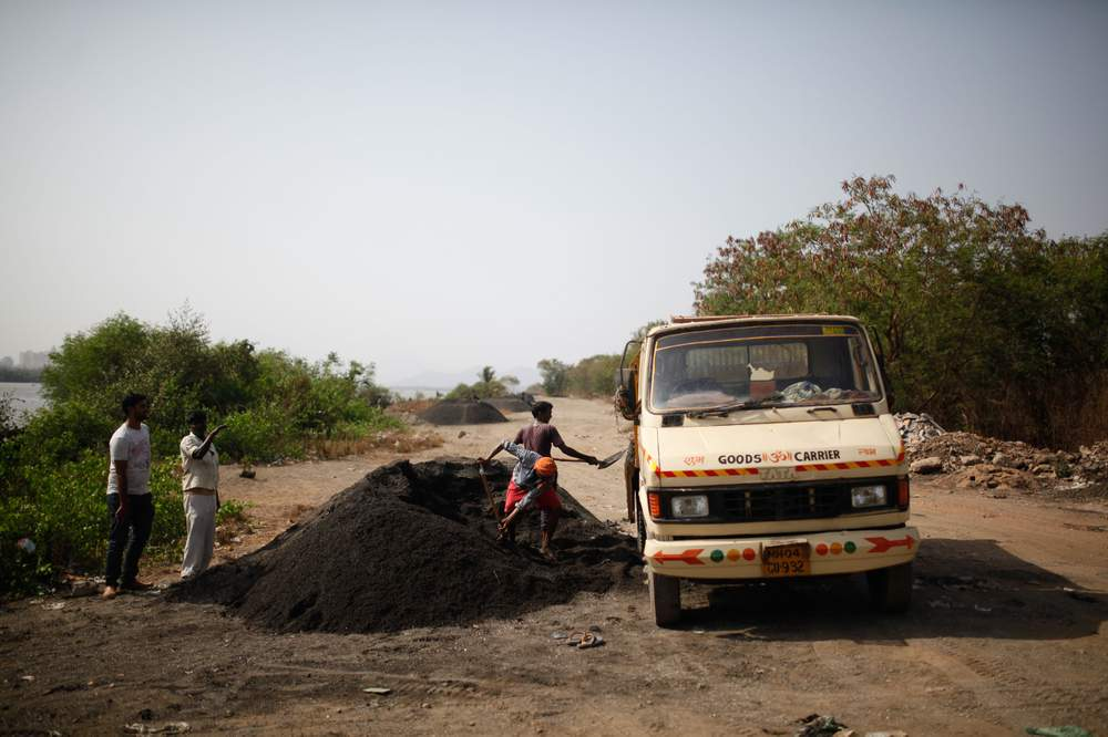 Workers load sand mined from the Vasai Creek on to a truck.