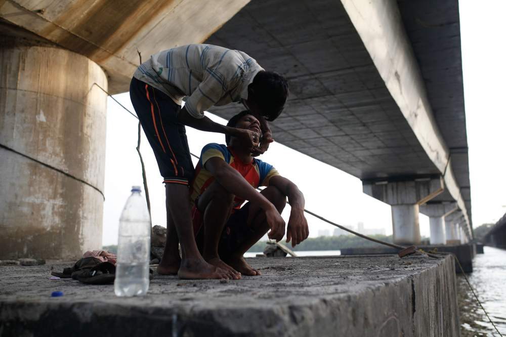 A sand miner shaves a fellow worker alongside the Vasai Creek.