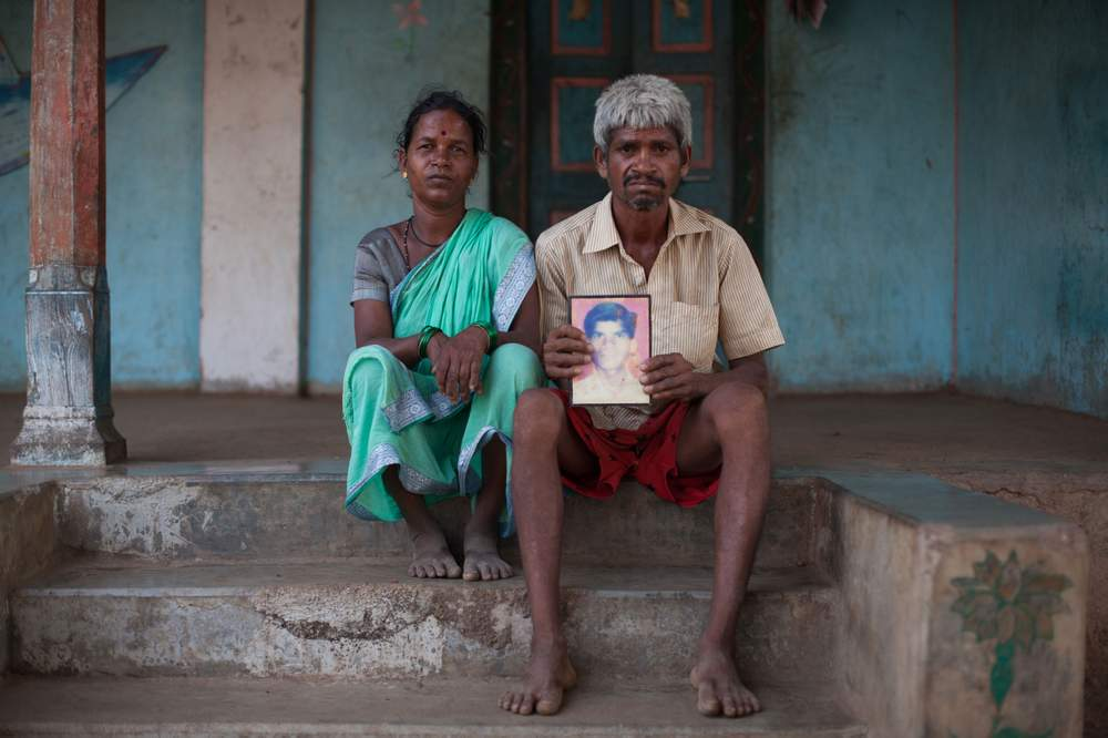 Chandrakant Shankar Meghwani and his wife Chandrakala pose with a picture of their son Mahesh who died while extracting sand.
