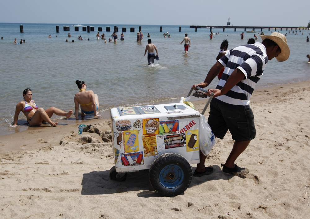 A vendor drags his ice cream cooler across North Avenue Beach in Chicago July 20, 2011, on a day when the heat index was expected to exceed 110 degrees Fahrenheit or 43 degrees Celsius.  REUTERS\/Jim Young