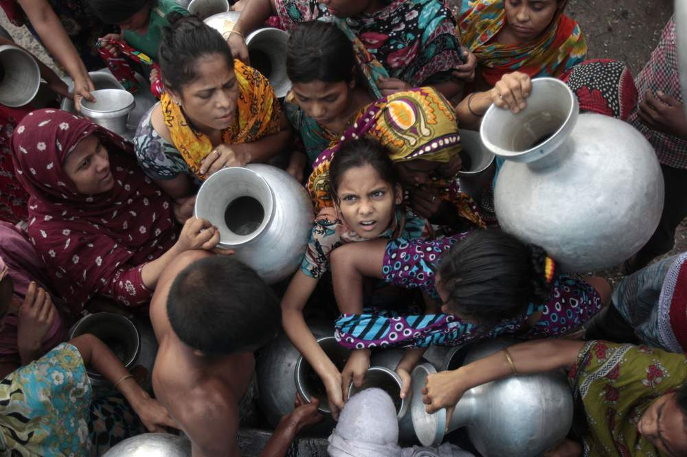 People holding water pots jostle as they collect water on the outskirts of Dhaka, May 28, 2012. REUTERS\/Andrew Biraj