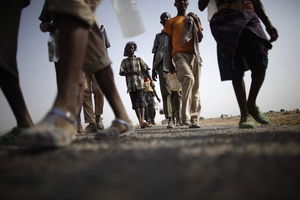 Ethiopian migrants walk on the side of a highway leading to the western Yemeni town of Haradh on the border with Saudi Arabia, March 28, 2012. REUTERS\/Khaled Abdullah