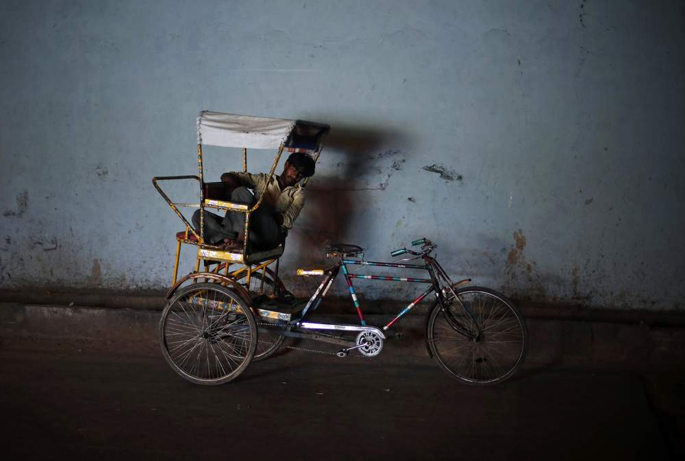 A man takes a nap on his cycle rickshaw under a bridge on a hot summer day in the old quarters of Delhi, June 11, 2014. REUTERS\/Adnan Abidi