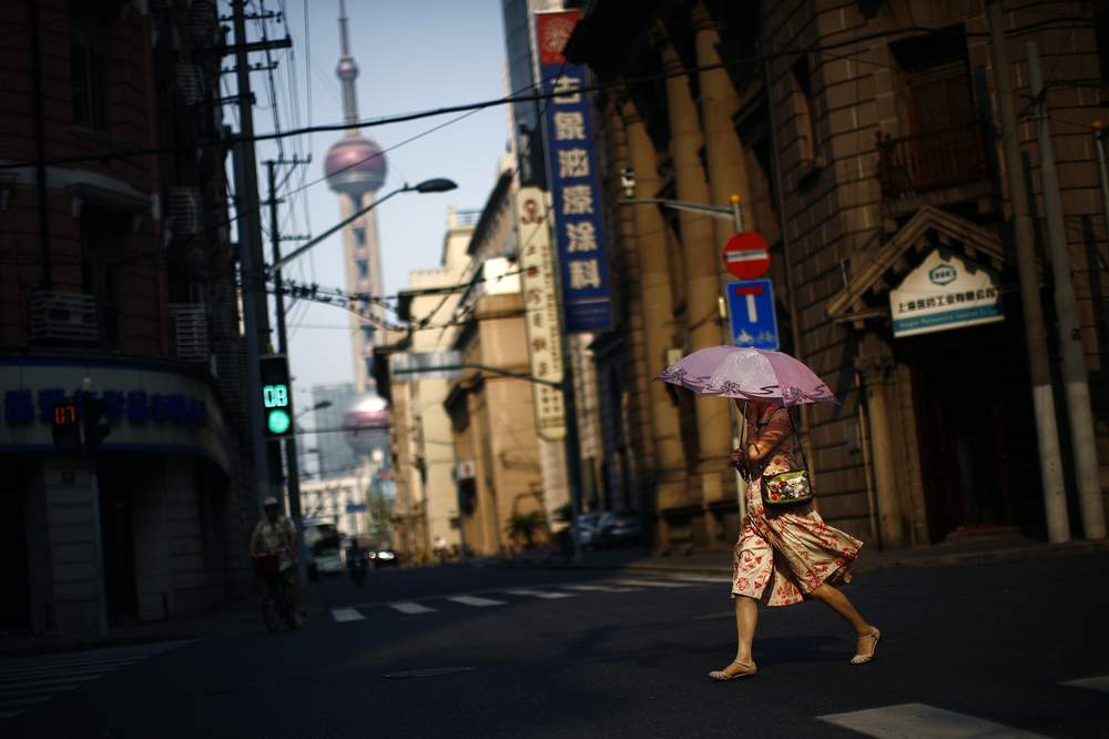 A woman uses an umbrella to protect herself from the sun as she crosses a busy street in downtown Shanghai, August 6, 2013. REUTERS\/Carlos Barria