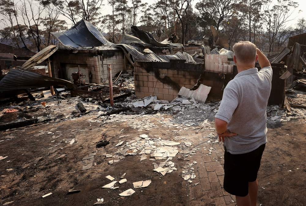 Colin Smith looks at the remains of his family's house after it was destroyed by a bushfire in the Blue Mountains suburb of Winmalee, located around 70 km west of Sydney, October 21, 2013. REUTERS\/David Gray