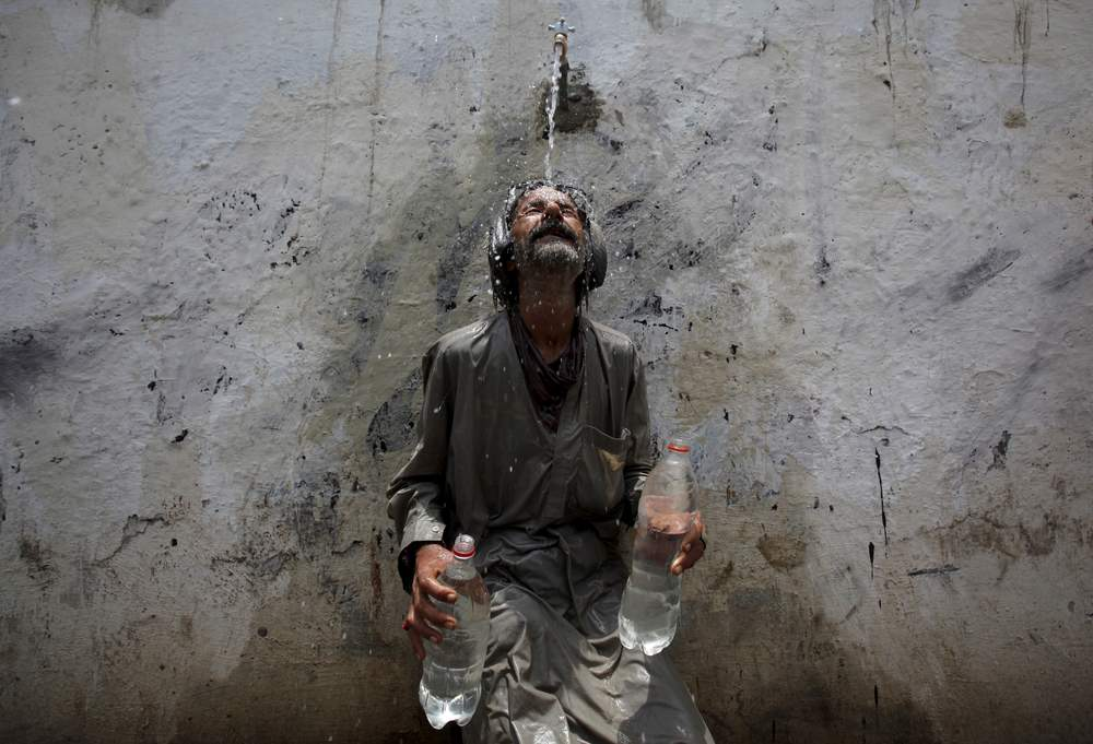 A man cools off from a public tap after filling bottles during intense hot weather in Karachi, Pakistan, June 23, 2015. REUTERS\/Akhtar Soomro