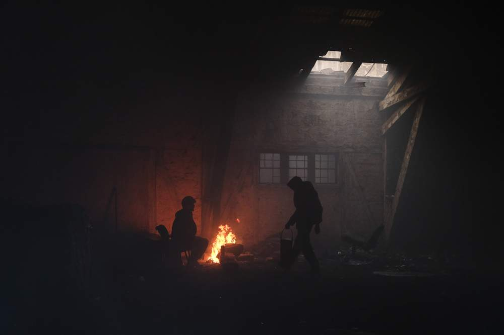 Migrants warm themselves around a fire in the abandoned warehouse where Ali lives.