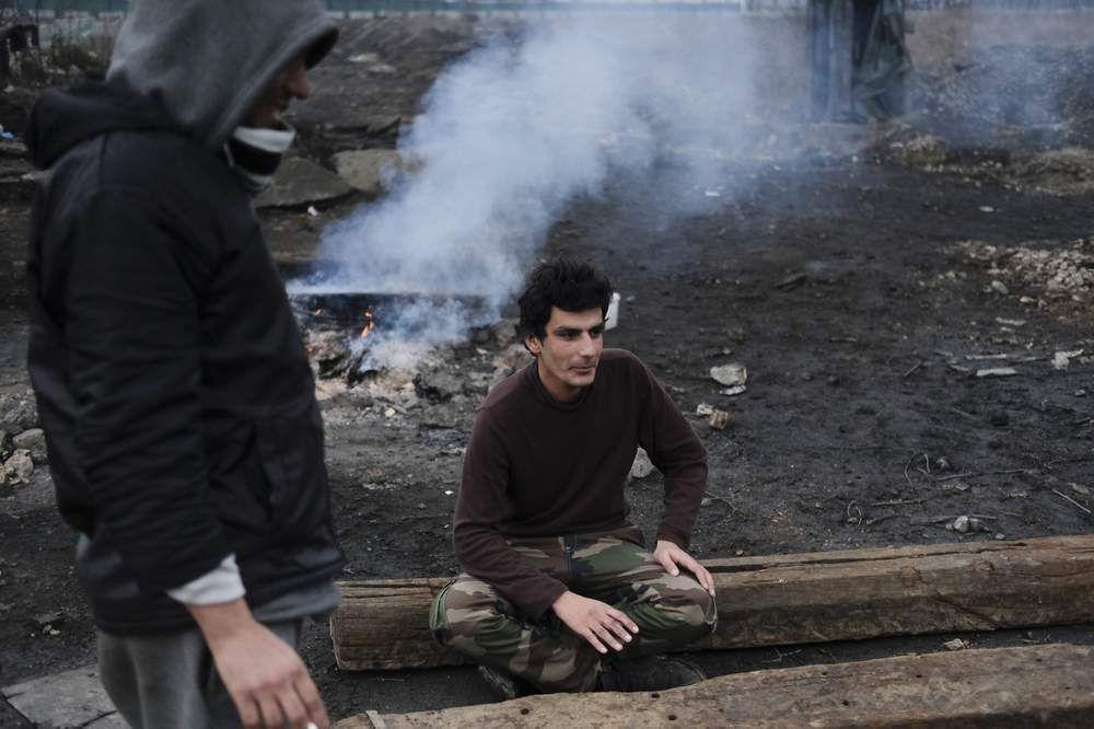 Ahmad Shakib sitting outside a large, abandoned warehouse near the main railway station in Serbia's capital Belgrade.