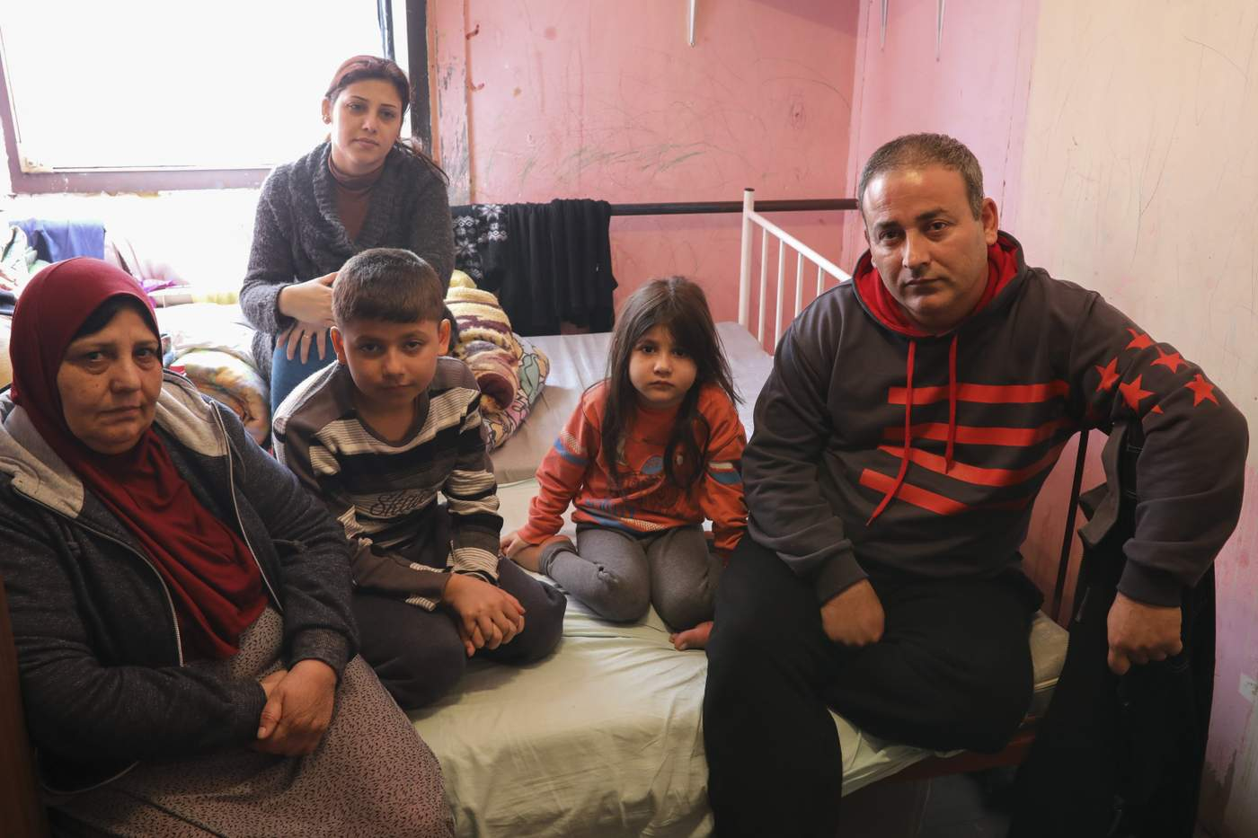 Aras Mahmoud, his wife, mother and children in their bedroom in a refugee centre in Krnjaca, Belgrade.