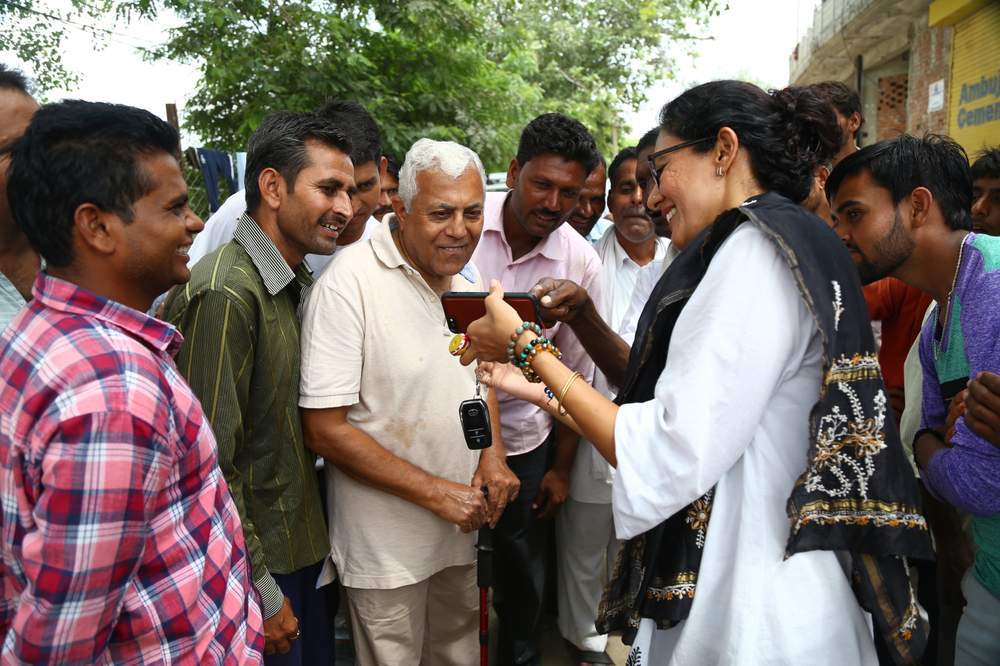 Village head Chhavi Rajawat shows her father [centre] and other villagers something on her phone.