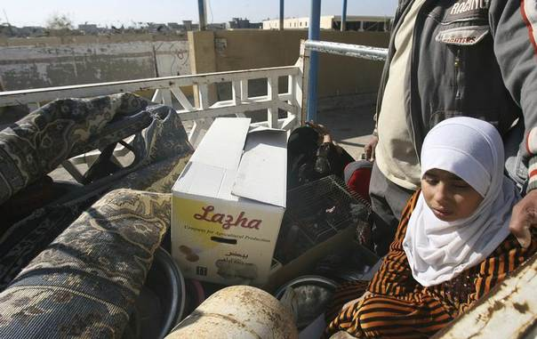 Iraqi Sunni families fleeing violence with their belongings stop at a checkpoint in the city of Falluja, 50 km (30 miles) west of Baghdad January 8, 2014. REUTERS/Stringer