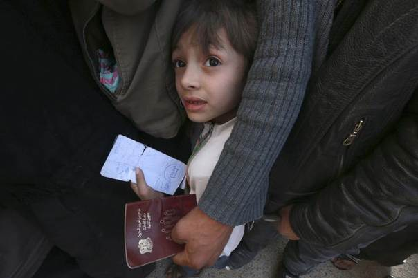 A boy carries identification papers while waiting in line to receive humanitarian aid in Duma, Damascus, March 29, 2014. Picture taken March 29, 2014. REUTERS/Bassam Khabieh