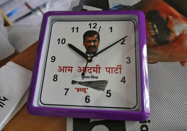 A wall clock carrying a portrait of Arvind Kejriwal, leader of the newly formed Aam Aadmi (Common Man) Party (AAP), and party symbol of a broom, lies on a table inside their party office in New Delhi October 1, 2013. REUTERS/Mansi Thapliyal