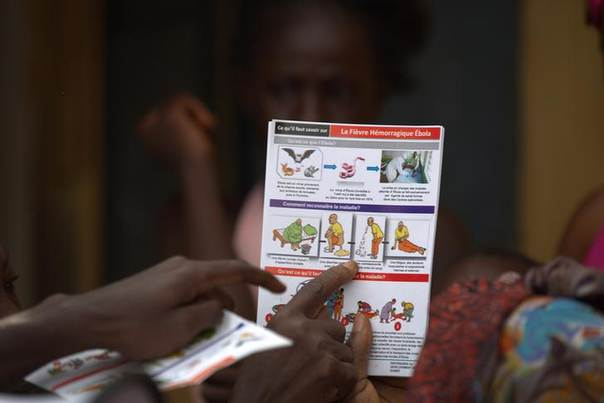 An aid worker shares information on Ebola and best practices to help prevent its spread with residents of the Matam neighborhood of Conakry, Guinea August 20, 2014. REUTERS/Timothy La Rose/UNICEF/Handout via Reuters