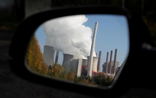 Rising steam from RWE coal power plant, is reflected in a car's mirror in Germany