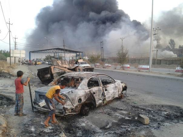 Children stand next to a burnt vehicle during clashes between Iraqi security forces and al Qaeda-linked Islamic State in Iraq and the Levant (ISIL) in the northern Iraq city of Mosul, June 10, 2014. REUTERS/Stringer