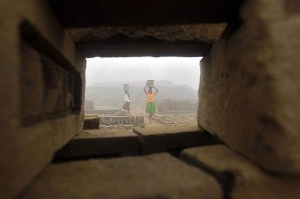 Woman labourers carry bricks at a brick factory amid fog on a cold winter morning on the outskirts of Agartala, the capital of India's northeastern state of Tripura, Jan. 7, 2014. REUTERS/Jayanta Dey