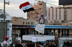 An Iraqi man holds an Iraqi flag as he celebrates the final victory over the Islamic State at Tahrir Square in Baghdad