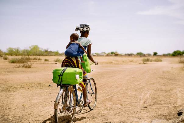 Barry Aliman, 24, rides her bicycle with her baby to collect water for her family near Boromo, Burkina Faso. A new online tool aims to paint a clear picture of how forests contribute to rural people's cliamte-adaptation strategies. Ollivier Girard/CIFOR photo