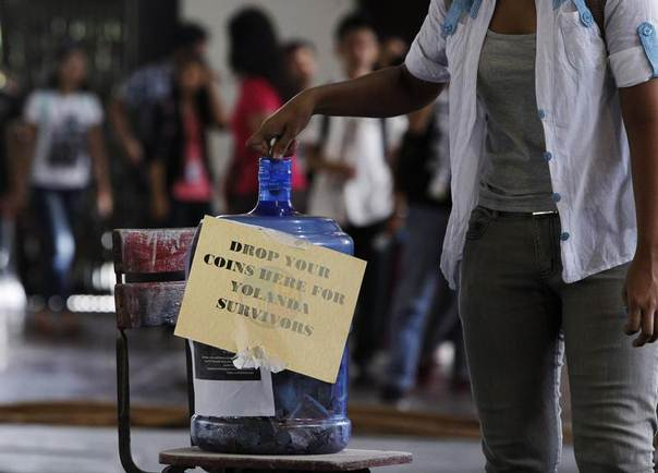 A student from the Polytechnic University of the Philippines drops loose change into a five-gallon mineral water container which has been converted into a coin bank for victims of Typhoon Haiyan, known locally as Yolanda, at the university grounds in Manila, Philippines, November 18, 2013. REUTERS/Romeo Ranoco