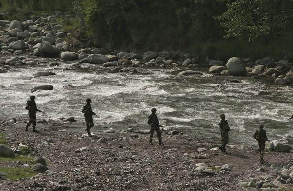 Indian Border Security Force (BSF) soldiers patrol next to a stream near the Line of Control (LoC), a ceasefire line dividing Kashmir between India and Pakistan, at Sabjiyan sector of Poonch district, August 8, 2013. REUTERS/Mukesh Gupta