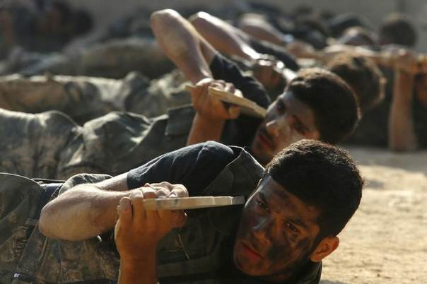 Rebel fighters demonstrate with their fake weapons during a military display as part of a graduating ceremony at a camp in eastern al-Ghouta, near Damascus August 31, 2014. REUTERS/Bassam Khabieh