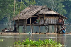 Villagers take shelter at a partially submerged house following floods at Baghmari village in Nagaon district, in the northeastern state of Assam, India