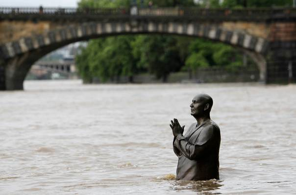 The statue of world harmony leader Sri Chinmoy is partially submerged in water from the rising Vltava river in Prague on June 2, 2013. Rivers across the Czech Republic are rising fast due to heavy rain. REUTERS/David W Cerny
