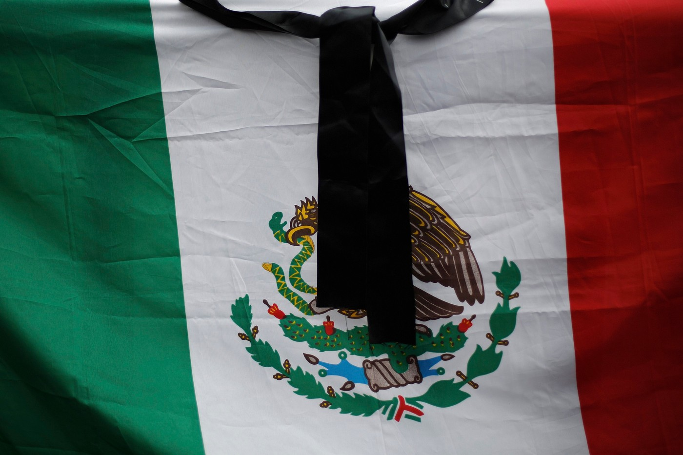 black ribbon is seen over a mexican flag during a protest for the
