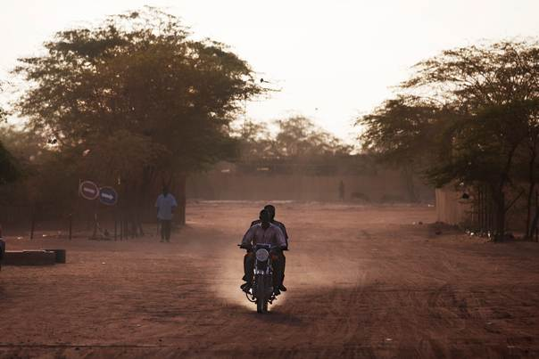 People ride a motorcycle down a dusty street in Niger, September 24, 2013. REUTERS/Joe Penney