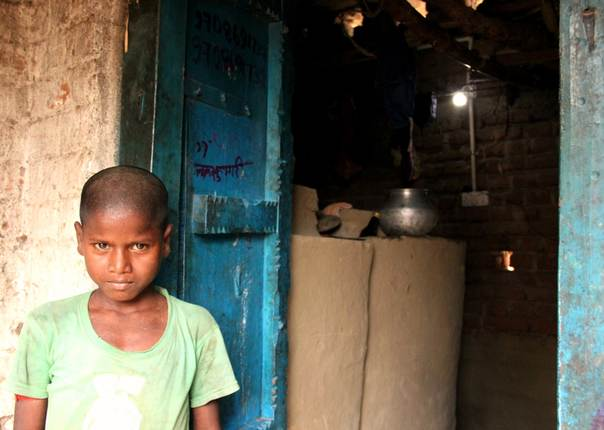Sanju Manjhi, the son of Suresh Manhji, stands in the doorway of his solar-power-lit home in Dharnai village, in India's Bihar state, in July 2014. THOMSON REUTERS FOUNDATION/Avik Roy