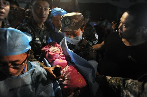 A baby born in a relief tent is attended by medical staff