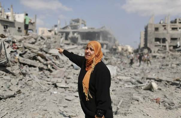 A Palestinian woman reacts as she stands next to her destroyed house in Beit Hanoun town, which witnesses said was heavily hit by Israeli shelling and air strikes during Israeli offensive, in the northern Gaza Strip July 26, 2014. REUTERS/Suhaib Salem