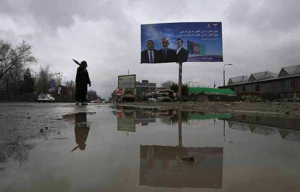 A man looks over his shoulder at an election advertisement for presidential candidate Ashraf Ghani in Kabul April 2, 2014. The Afghan presidential elections will be held on April 5. REUTERS/Tim Wimborne