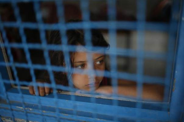 A Palestinian girl, who fled her house during an Israeli offensive, looks out of a classroom window at a United Nations-run school sheltering displaced Palestinians in Jabaliya refugee camp in the northern Gaza Strip August 3, 2014. REUTERS/Mohammed Salem