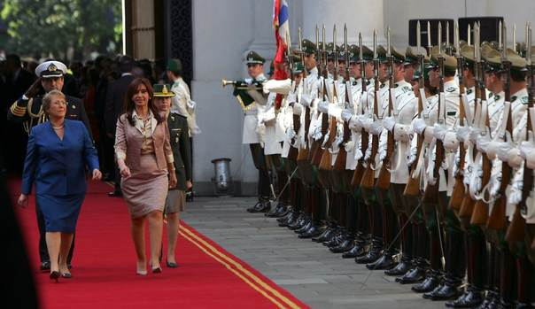 In a 2008 file photo, then president of Chile Michelle Bachelet (L) and her Argentine counterpart Cristina Fernandez de Kirchner walk past an honor guard at La Moneda Presidential Palace in Santiago. Bachelet was re-elected president and will take office again in March 2014. REUTERS/Victor Ruiz Caballero