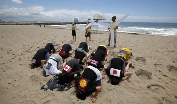 Environmental activists bury their heads in the sand on Durban's beachfront, December 2, 2011. The demostration aimed to highlight nations failing to act effectively to prevent climate change. REUTERS/Mike Hutchings