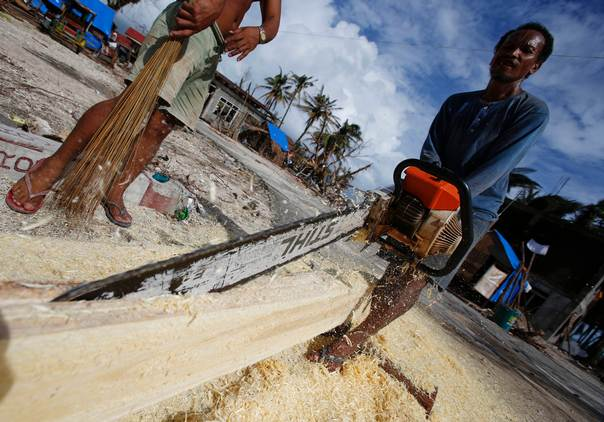 A man cuts a tree trunk that fell during Super Typhoon Haiyan into planks to be used as house-building material in the eastern Samar coastal village of Hernani, the Philippines, on November 20, 2013. REUTERS/Wolfgang Rattay