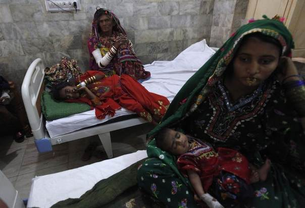 Kari, a nine-year-old suffering from a stomach infection, lies beside her mother at a hospital in Mithi in Pakistan's Sindh province, amid a drought that caused dozens of children to die of malnutrition and other causes, March 11, 2014. REUTERS/Akhtar Soomro