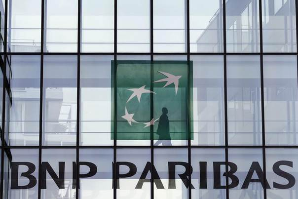 An employee walks behind the logo of BNP Paribas in a company's building in Issy-les-Moulineaux, near Paris, June 2, 2014 REUTERS/Charles Platiau