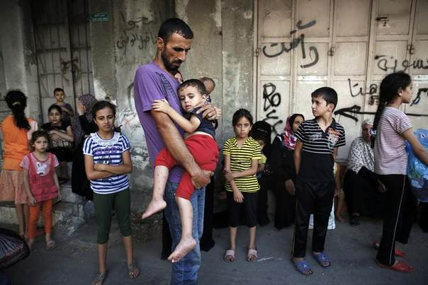 A Palestinian man holds a child while fleeing the Shujayeh neighbourhood during heavy Israeli shelling in Gaza City July 20, 2014. . REUTERS/Finbarr O'Reilly