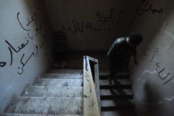 A soldier loyal to Syrian President Bashar al-Assad walks down flights of stairs in the Armenian Christian town of Kasab June 16, 2014. REUTERS/Omar Sanadiki