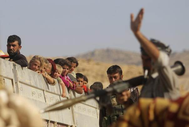 A Yazidi fighter who recently joined the Kurdish People's Protection Units (YPG) gestures while securing a road in Mount Sinjar in northern Iraq for displaced people from the Yazidi religious minority fleeing violence from forces loyal to the Islamic State in Sinjar town, as they make their way towards Newrooz camp in Syria's al-Hasakah province August 13, 2014. REUTERS/Rodi Said