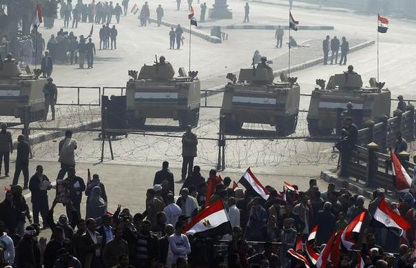 Supporters of Egypt's army and police cheer with national flags in front of armoured personnel carriers (APC) in front of Tahrir square in Cairo, on the third anniversary of Egypt's uprising, January 25, 2014. REUTERS/Amr Abdallah Dalsh