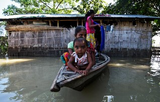 Villagers use a boat as they try to move to safer places at a flood-affected village