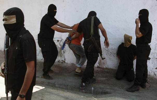 Hamas militants surround Palestinians suspected of collaborating with Israel before executing them in Gaza City August 22, 2014. REUTERS/Stringer