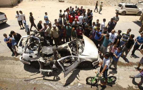 Palestinians gather around the remains of a car which police said was targeted in an Israeli air strike, in the northern Gaza Strip July 10, 2014. REUTERS/Ahmed Zakot