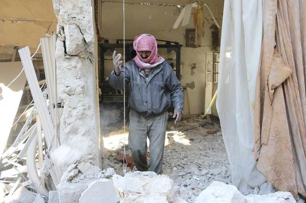 A man stands amid the rubble of damaged buildings at a site hit by what activists said was a barrel bomb dropped by forces loyal to Syria's President Bashar al-Assad in Masaken Hanano in Aleppo February 17, 2014. REUTERS/Hosam Katan