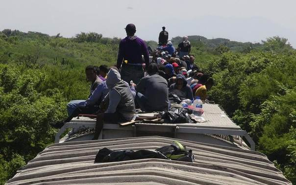 Unaccompanied minors ride atop the wagon of a freight train, known as La Bestia (The Beast) in Ixtepec, in the Mexican state of Oaxaca, June 18, 2014. REUTERS/Jose de Jesus Cortes