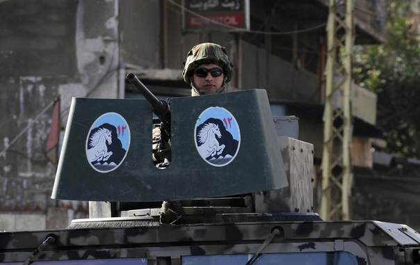A Lebanese army soldier is seen on a military vehicle while patrolling a street in the Sunni Muslim Bab al-Tebbaneh neighbourhood in Tripoli, northern Lebanon, January 21, 2014. REUTERS/Omar Ibrahim
